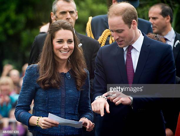 Catherine Duchess of Cambridge and Prince William Duke of Cambridge look at the friendship bands they were given during a walk about in Civic Square...