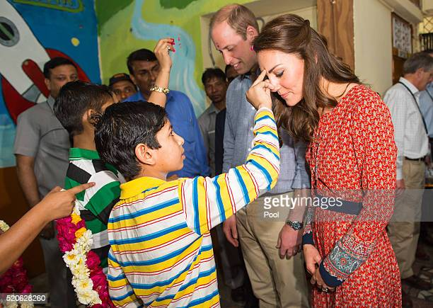 Catherine Duchess of Cambridge and Prince William Duke of Cambridge are greeted with a tilak at a contact centre run by the charity Salaam Baalak...