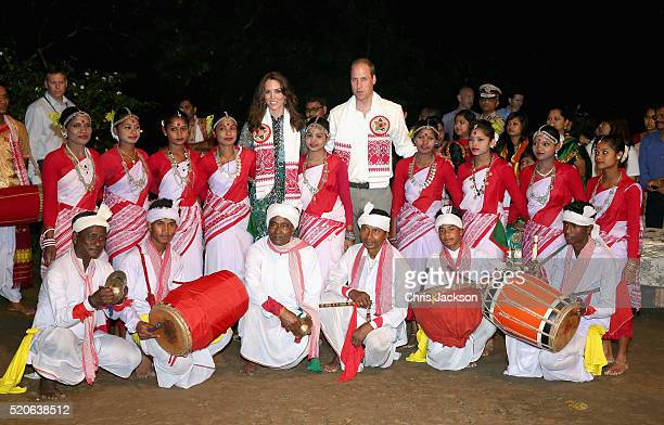 Catherine Duchess of Cambridge and Prince William Duke of Cambridge pose with dancers by the fireside during a Bihu Festival Celebration at Diphlu...