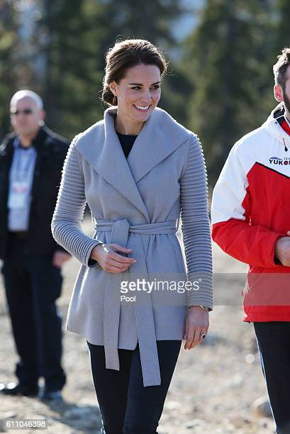 Catherine, Duchess of Cambridge and Prince William, Duke of Cambridge talk to locals about mountain bikes on Montana mountain near Carcross during...