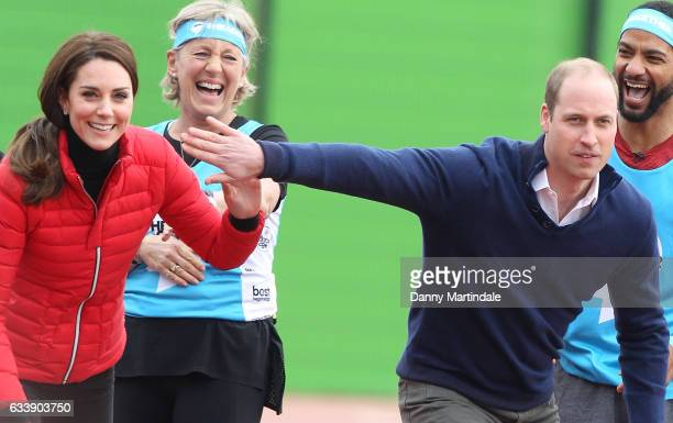 Catherine Duchess of Cambridge and Prince William Duke of Cambridge play about before they run a race during a training day for the Heads Together...