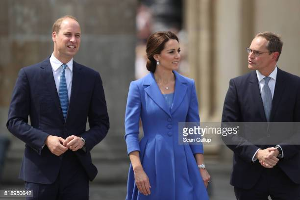 Catherine Duchess of Cambridge and Prince William Duke of Cambridge walk with Berlin Mayor Michael Mueller upon their arrival at the Brandenburg Gate...