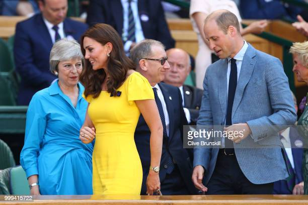 Catherine Duchess of Cambridge and Prince William Duke of Cambridge pass British Prime Minister Theresa May and her husband Philip May as they attend...