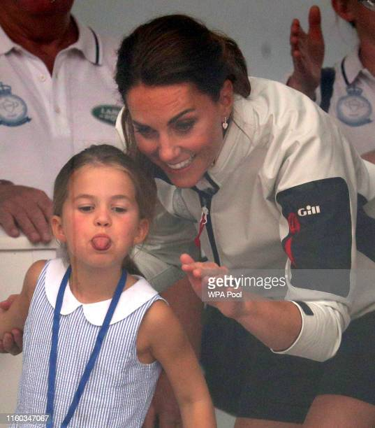 Catherine, Duchess of Cambridge and Princess Charlotte of Cambridge look through a window at the prize giving after the King's Cup regatta on August...