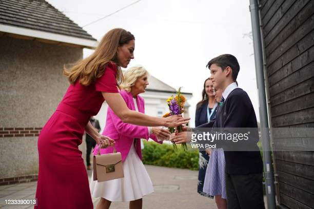 Catherine, Duchess of Cambridge and U.S. First Lady Dr Jill Biden presented with flowers by the head boy and head girl during a visit to Connor Downs...