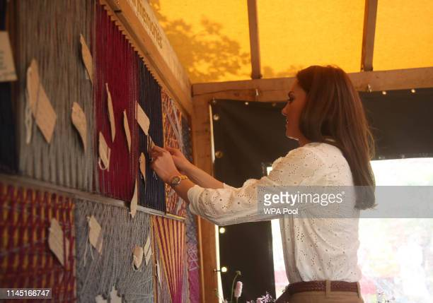 Catherine Duchess of Cambridge attaches her message to a board during her visit to the RHS Chelsea Flower Show at the Royal Hospital Chelsea on May...