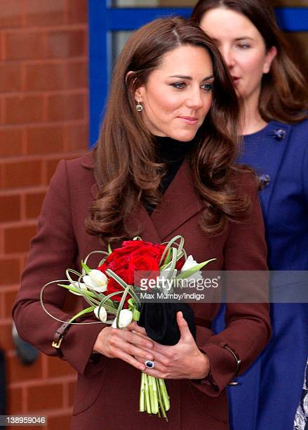 Catherine, Duchess of Cambridge carries a posy of red roses and white tulips as she leaves Alder Hey Children's Hospital on February 14, 2012 in...