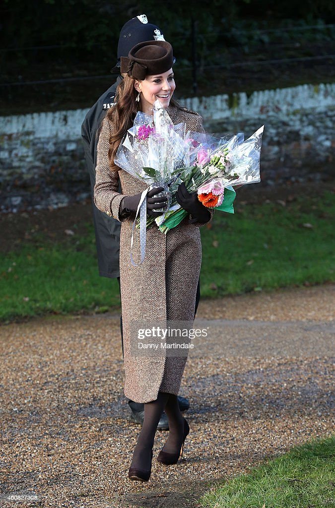 Catherine, Duchess of Cambridge carries bouquets of flowers as she attends a Christmas Day church service at Sandringham on December 25, 2014 in King's Lynn, England.