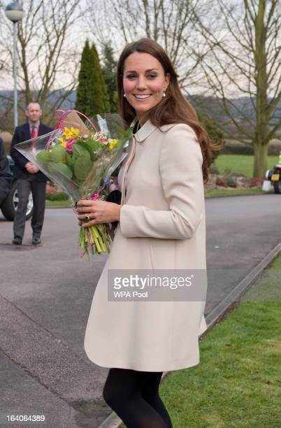 Catherine Duchess of Cambridge carries flowers as she visits the offices of Child Bereavement UK on March 19 2013 in Saunderton Buckinghamshire