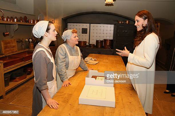 Catherine, Duchess of Cambridge chats to actresses Sopie McShera and Lesley Nicol during an official visit to the set of Downton Abbey at Ealing...