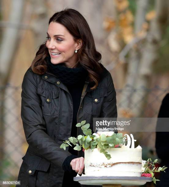 Catherine Duchess of Cambridge cuts a cake as she visits the Robin Hood Primary School to celebrate ten years of The Royal Horticultural Society...