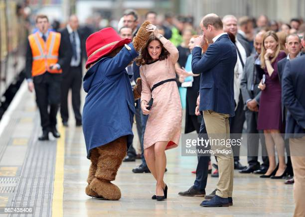 Catherine Duchess of Cambridge dances with Paddington Bear watched by Prince William Duke of Cambridge and Prince Harry as they attend the Charities...
