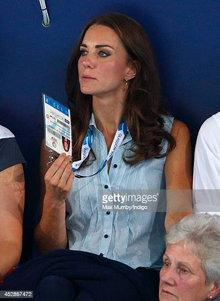 Catherine Duchess of Cambridge fans herself with her Commonwealth Games accreditation as she watches the swimming at the Tollcross International...