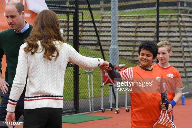 Catherine, Duchess of Cambridge fist bumps a schoolchild during a tennis game as they take part in the Lawn Tennis Association's Youth programme, at...