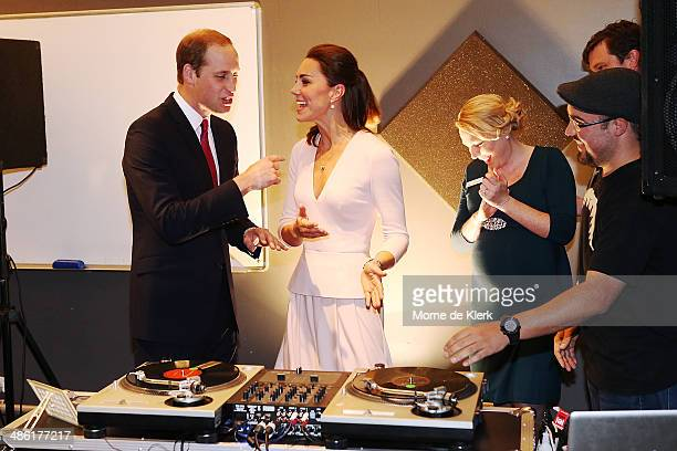 Catherine Duchess of Cambridge gestures to Prince William Duke of Cambridge to play on DJ decks at the Northern Sound System on April 23 2014 in...