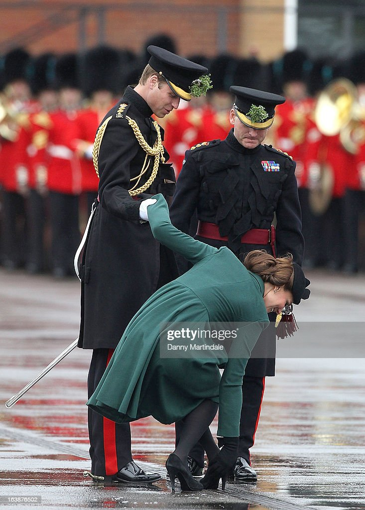 Catherine, Duchess of Cambridge gets her shoe stuck in the grating and is helped by Prince William, Duke of Cambridge at a St Patrick's Day parade on March 17, 2013 in Aldershot, England.