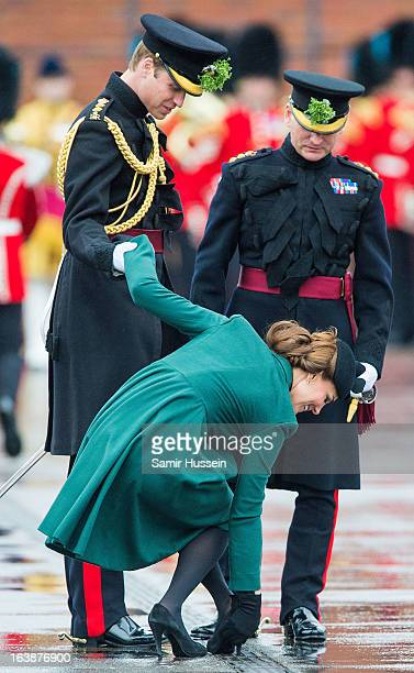 Catherine, Duchess of Cambridge gets her shoe stuck in the grating and is helped by Prince William, Duke of Cambridge as they visit the Irish Guards'...