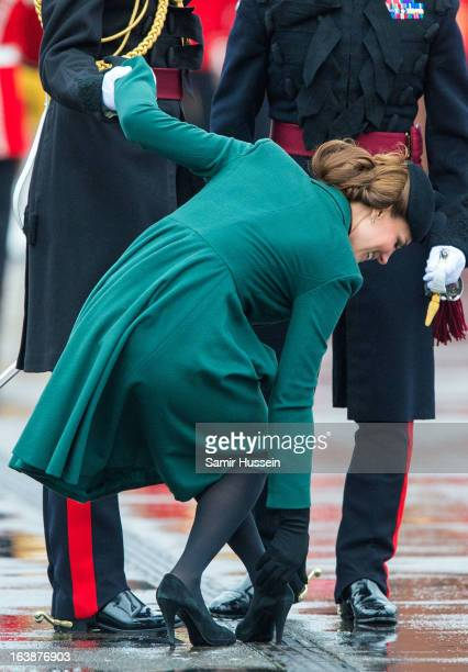 Catherine Duchess of Cambridge gets her shoe stuck in the grating and is helped by Prince William Duke of Cambridge as they visit the Irish Guards'...