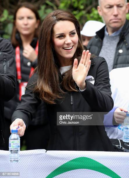 Catherine Duchess of Cambridge hands out water to runners during the 2017 Virgin Money London Marathon on April 23 2017 in London England The Duke...