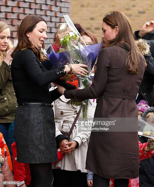 Catherine Duchess of Cambridge hands Rebecca Deacon flowers she received from local children as she attends an event hosted by The Fostering Network...