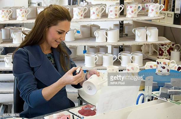 Catherine Duchess of Cambridge helps decorate a mug as she visits the 'Emma Bridgewater' pottery factory to view the production of a mug that the...