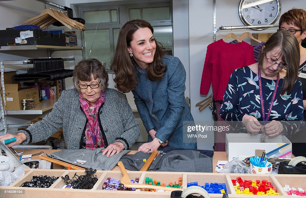 Catherine, Duchess of Cambridge helps to sort clothes as she takes a tour of the new EACH charity shop that she officially opened earlier today on March 18, 2016 in Holt, United Kingdom.