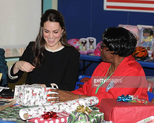 Catherine Duchess of Cambridge helps to wrap Christmas presents during a visit to the Northside Center for Child Development on December 8 2014 in...