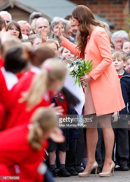 Catherine Duchess of Cambridge 'high fives' a young child as she meets local school children on a visit to Naomi House Children's Hospice to...