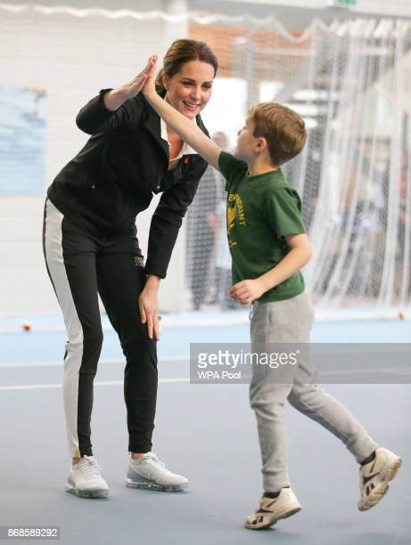 Catherine Duchess of Cambridge highfives a boy as she takes part in a Tennis for Kids session during a visit at the Lawn Tennis Association at the...