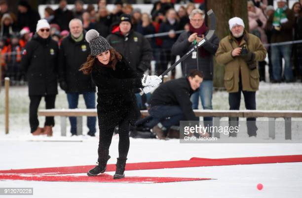 Catherine Duchess of Cambridge hits the ball as she attends a Bandy hockey match with Prince William Duke of Cambridge where they will learn more...