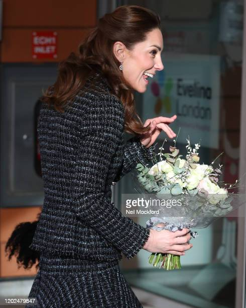 Catherine Duchess of Cambridge holds a bouquet as she arrives to join a workshop run by the National Portrait Gallery's Hospital Programme at Evelina...