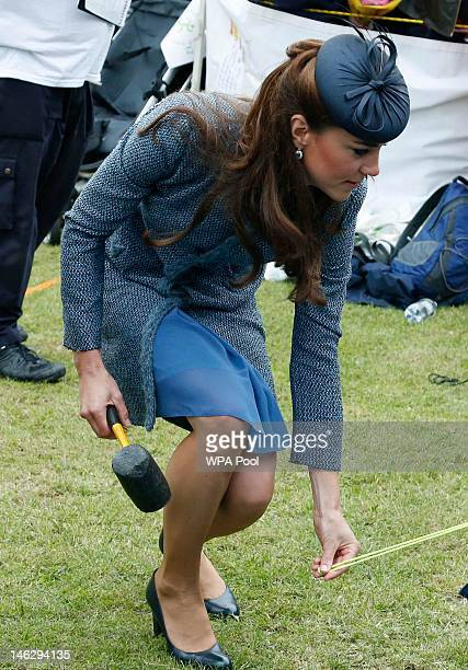 Catherine, Duchess of Cambridge holds a mallet as she helps scouts erect a tent as part of a children's sports event while visiting Vernon Park...
