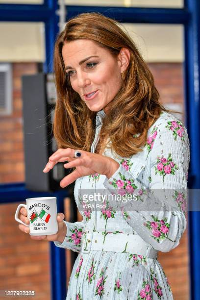 Catherine Duchess of Cambridge holds a Marco's Cafe mug while chatting with business owners inside Marco's cafe during the Duke and Duchess of...