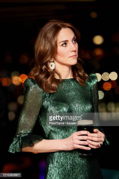 Catherine, Duchess of Cambridge holds a pint of Guinness as she visits the Guinness Storehouse's Gravity Bar during day one of their visit to Ireland...