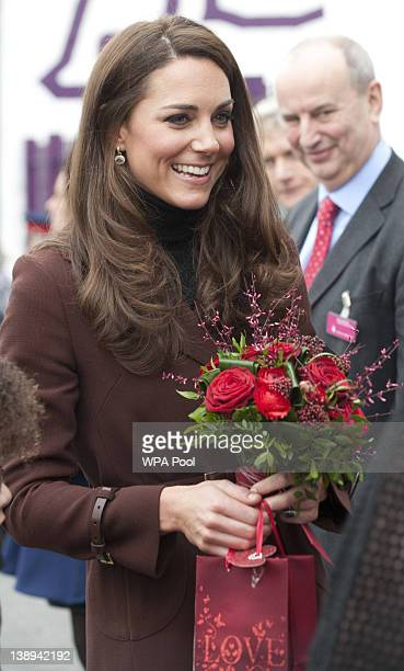 Catherine Duchess of Cambridge holds a posey of red roses presented to her by Eightyearold Jaqson JohnstonLynch after her visit to charity The Brink...