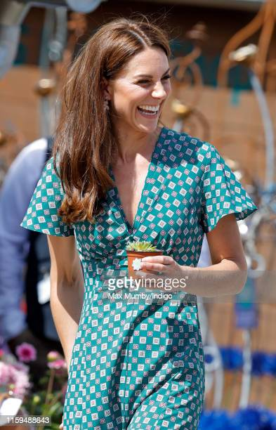 Catherine, Duchess of Cambridge holds a potted succulent plant as she visits the RHS Hampton Court Palace Garden Festival to view the RHS 'Back to...