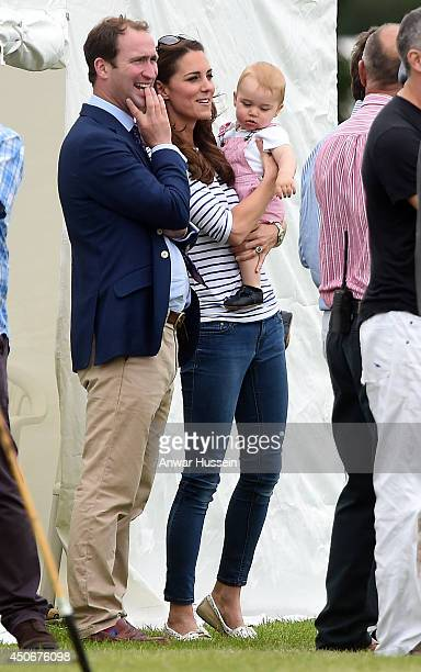 Catherine Duchess of Cambridge holds baby Prince George as they watch Prince William Duke of Cambridge and Prince Harry play in a charity polo match...