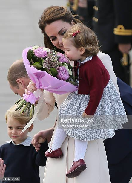 Catherine Duchess of Cambridge holds flowers up to Princess Charlotte of Cambridge as they depart Victoria on October 1 2016 in Victoria Canada