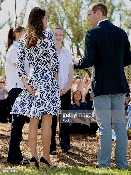 Catherine Duchess of Cambridge holds onto her dress as the wind blows as the Duke and Duchess of Cambridge meet Winmalee Girl Guides at Winmalee...