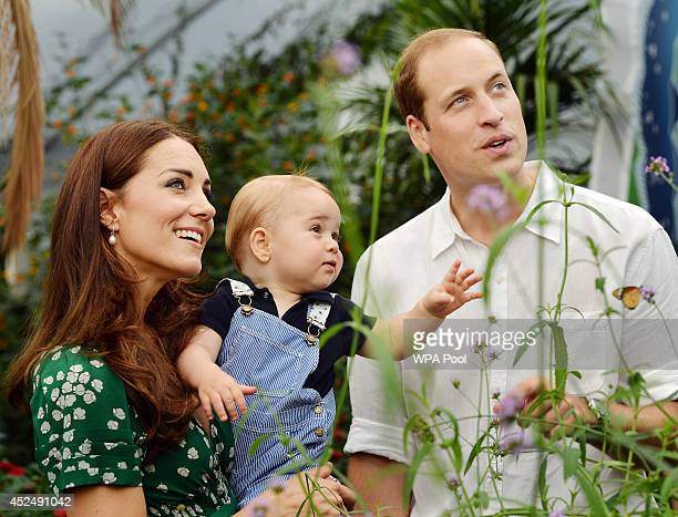 Catherine, Duchess of Cambridge holds Prince George as he and Prince William, Duke of Cambridge's look on while visiting the Sensational Butterflies...
