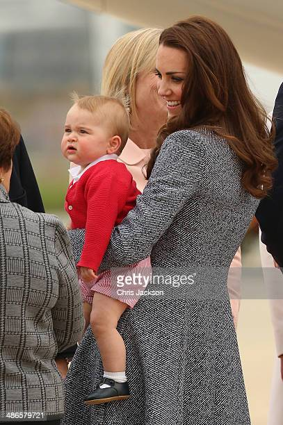Catherine, Duchess of Cambridge holds Prince George of Cambridge as they leave Fairbairne Airbase to head back to the UK after finishing their Royal...