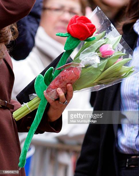 Catherine, Duchess of Cambridge holds some flowers and a bag of jelly sweets given to her by members of the public as she visits Alder Hey Children's...