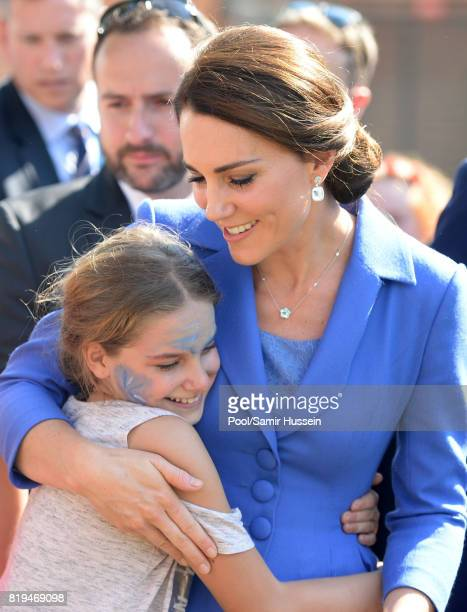 Catherine Duchess of Cambridge hugs a child as she visits Strassenkinder a charity which supports young people from disadvantaged backgrounds during...