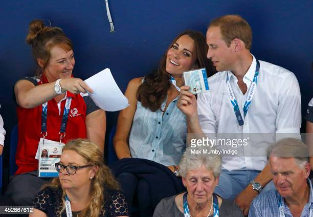 Catherine Duchess of Cambridge is fanned by a Commonwealth Games worker and Prince William Duke of Cambridge as they watch the swimming at the...