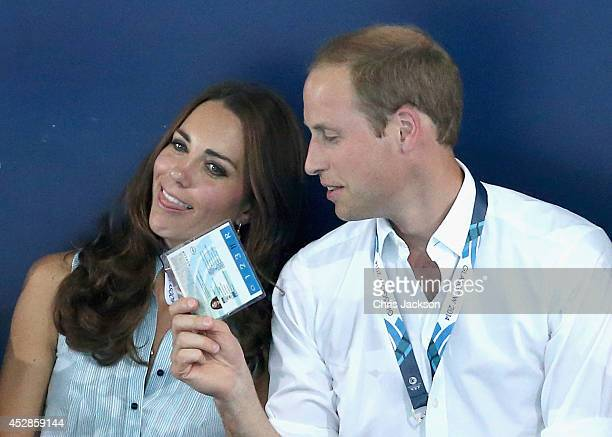 Catherine Duchess of Cambridge is fanned in the heat of Tollcross Swimming Centre by Prince William Duke of Cambridge and a Games Volunteer as they...