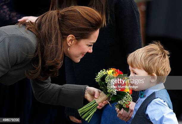 Catherine Duchess of Cambridge is given a posy of flowers as she undertakes a walkabout in Castle Square Caernarfon during a day of engagements in...