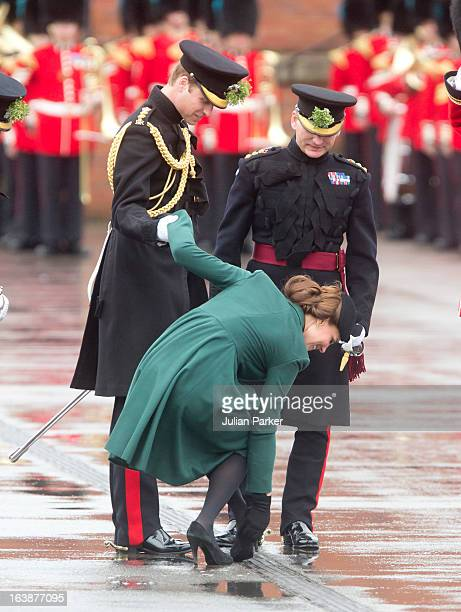 Catherine, Duchess of Cambridge is helped by Prince William, Duke of Cambridge as her heel gets stuck in the grating while attending The Irish Guards...