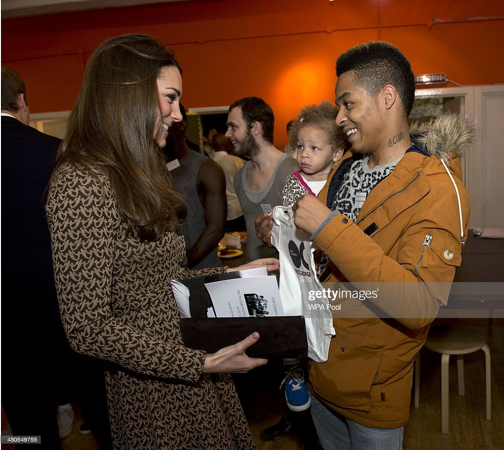 Catherine, Duchess of Cambridge is presented with a baby grow for her son Prince George of Cambridge from Aaron Russell-Andrews and his daughter Teegan at the Only Connect and ex-offenders projects on November 19, 2013 in London, England. Their Royal Highnesses also visited two further complimentary projects Bounce Back and Handmade Alliance, also based at the head office premises, before moving to a nearby Only Connect project venue to watch a dance performance.