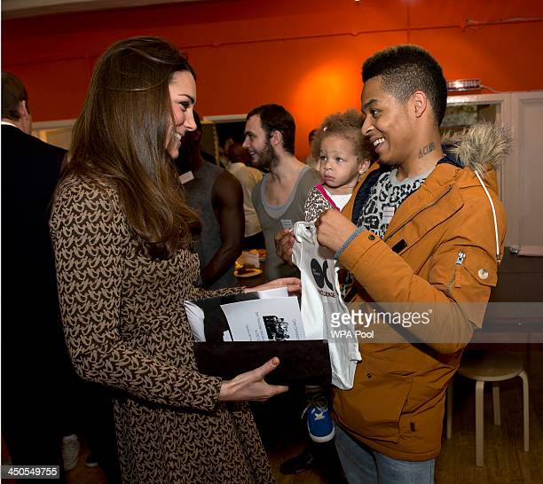 Catherine, Duchess of Cambridge is presented with a baby grow for her son Prince George of Cambridge from Aaron Russell-Andrews and his daughter...