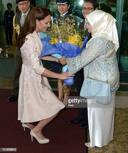 Catherine Duchess of Cambridge is presented with a bouquet of flowers as she arrives at Singapore Changi Airport during the Diamond Jubilee tour on...